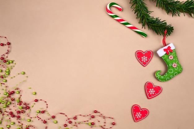 Grânulos de natal festivos, uma bota vermelho-verde para doces pendurados em um galho de árvore de natal, com um pirulito deitado na forma de uma bengala, com um coração vermelho, sobre um fundo bege