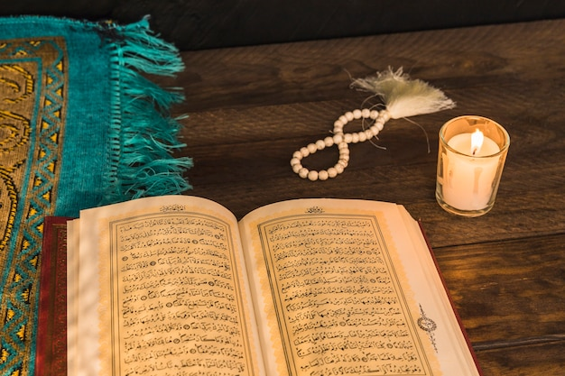 Grânulos de oração e vela perto de livro religioso