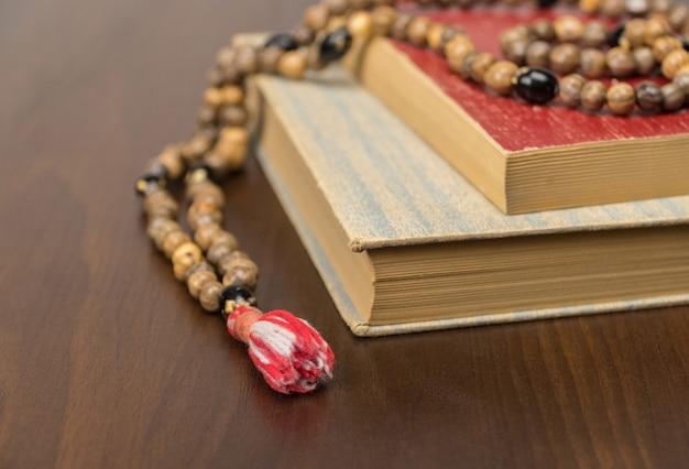 Grânulos de oração muçulmanos e alcorão isolados em um fundo de madeira. conceitos islâmicos e muçulmanos