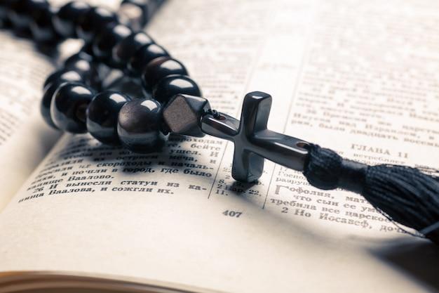 Grânulos de pedra preta do cristianismo com cruz na bíblia
