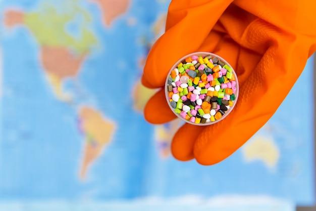 Grânulos de plástico nas mãos com luvas laranja no fundo do mapa mundial