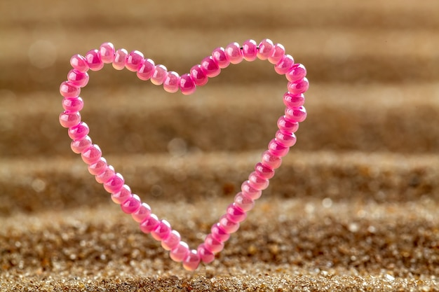 Grânulos em forma de coração de presente em um fundo de areia.