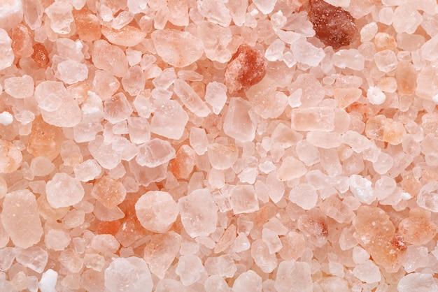 Grânulos grossos de sal rosa do himalaia close-up macro plano de fundo ou textura