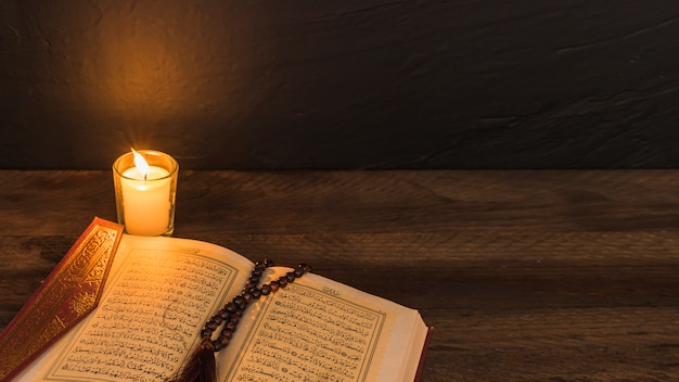 Grânulos no livro religioso perto de vela