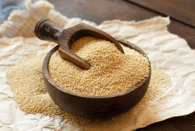 Grão de amaranto orgânico cru em uma tigela na mesa de madeira