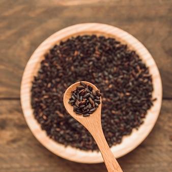 Grão de arroz orgânico preto na colher sobre a tigela no pano de fundo de madeira