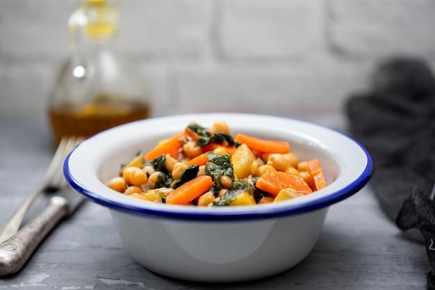 Grão de bico com cenoura e espinafre na tigela branca
