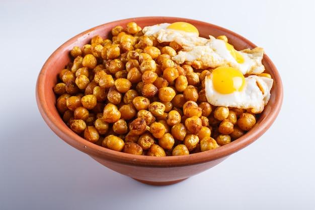 Grão de bico frito com ovos de codorna e especiarias em um prato de barro, isolado no fundo branco