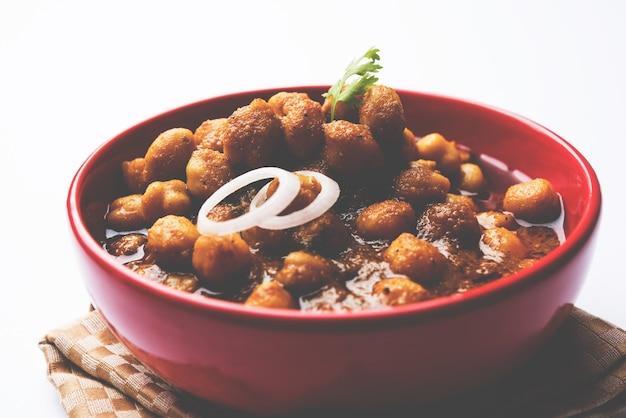 Grão de bico masala - chole masala ou curry choley, almoço tradicional do norte da índia, menu de jantar servido em uma tigela de cerâmica, foco seletivo