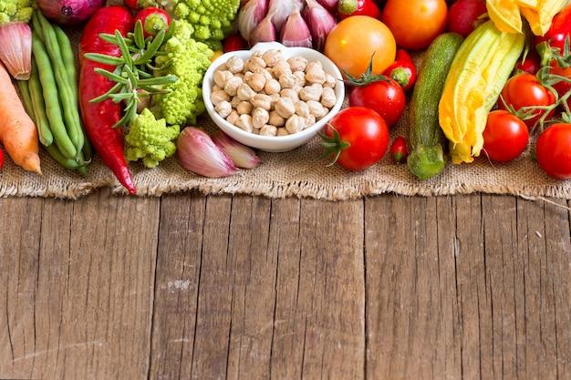 Grão de bico orgânico seco em uma tigela com vegetais crus em uma mesa de madeira perto com espaço de cópia