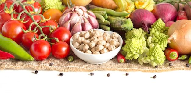 Grão de bico seco cru e legumes isolados no branco close-up
