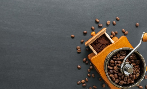 Grão de café e moedor manual na mesa preta