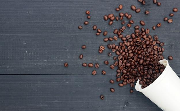 Grão de café em copo quente branco sobre fundo preto de madeira