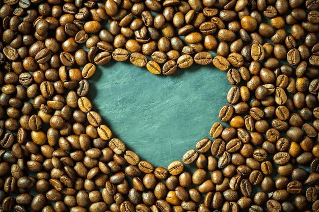 Grão de café em forma de coração na mesa de madeira. conceito eu amo fundo de café