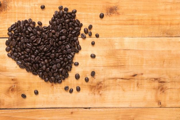 Grão de café em forma de corações na madeira de fundo marrom, cópia espaço para apresentação