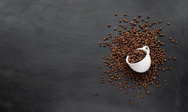 Grão de café em xícara branca no chão de cimento preto