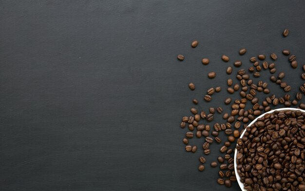 Grão de café em xícara branca no chão de madeira preta