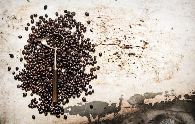 Grão de café torrado com uma colher. sobre fundo rústico.