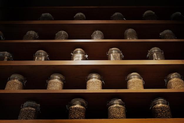 Grão de café torrado em caixa de vidro na prateleira de madeira