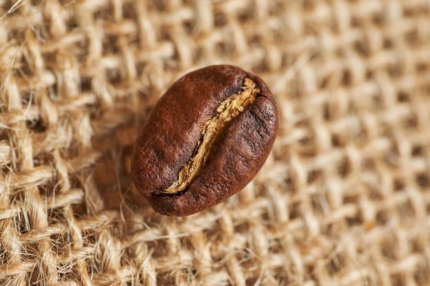 Grão de café torrado em tecido de malha. vista do topo.