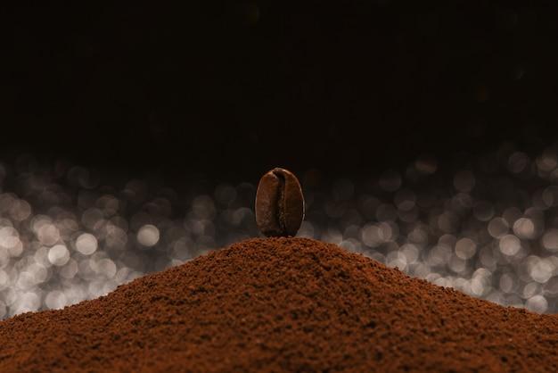 Grão de café torrado fresco fica em um punhado de café moído em um fundo preto e branco bokeh