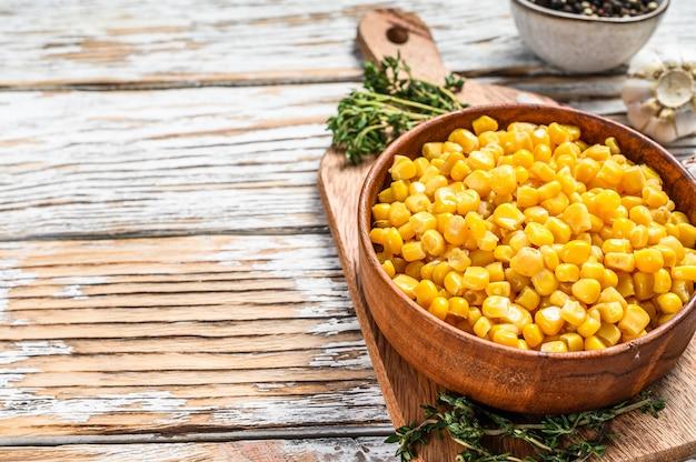 Grão de milho em conserva na tigela sobre um fundo de madeira. comida enlatada. vista superior. copie o espaço