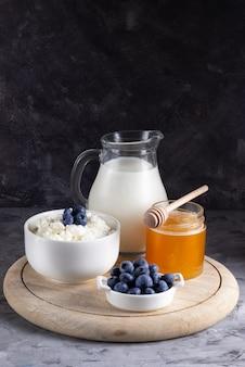 Grão de queijo cottage em uma tigela branca com uma jarra de leite em um fundo claro