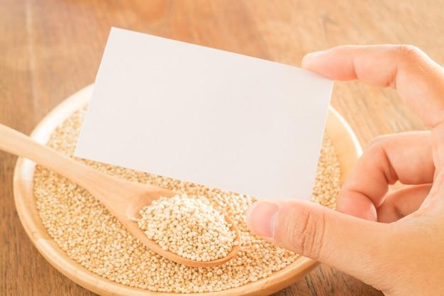 Grão de quinoa orgânica e mão no cartão