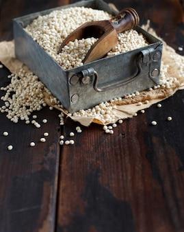 Grão de sorgo branco cru em uma caixa de metal sobre uma mesa de madeira escura