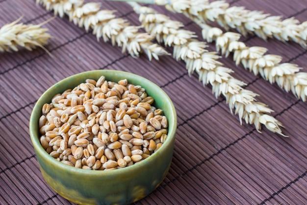 Grão de trigo em uma caixa verde, um ramo de trigo em uma mesa marrom