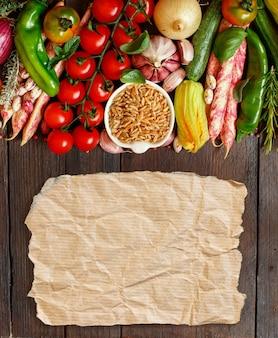 Grão kamut cru com legumes e papel na madeira