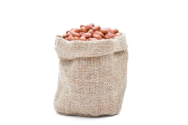 Grãos crus de amendoim em um saco de fundo branco