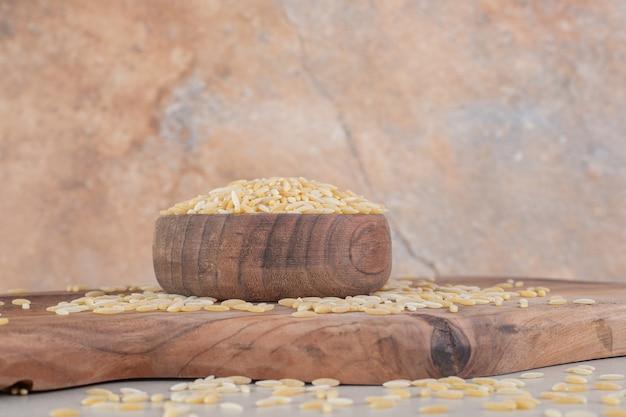 Grãos de arroz amarelo em uma xícara de madeira rústica.
