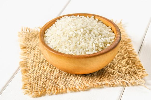 Grãos de arroz branco cru em uma mesa de madeira branca de tábuas. ingredientes para cozinhar.
