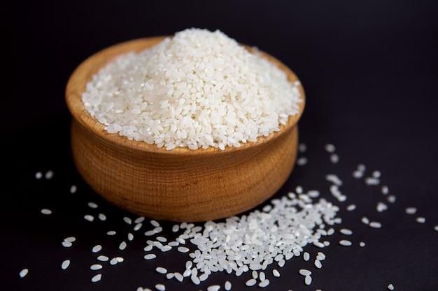 Grãos de arroz branco em uma tigela de madeira elegante