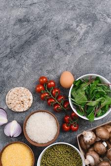 Grãos de arroz; brotos de feijão; bolo de arroz tufado; polenta; tomate cereja; ovo; cebola cortada ao meio e cogumelo contra o pano de fundo concreto