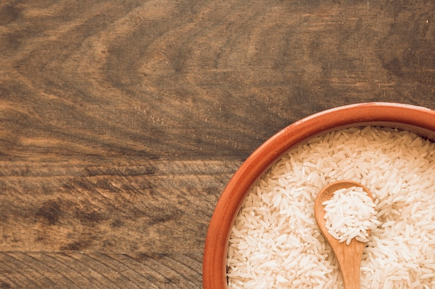 Grãos de arroz cru com colher de pau, sobre o fundo de madeira
