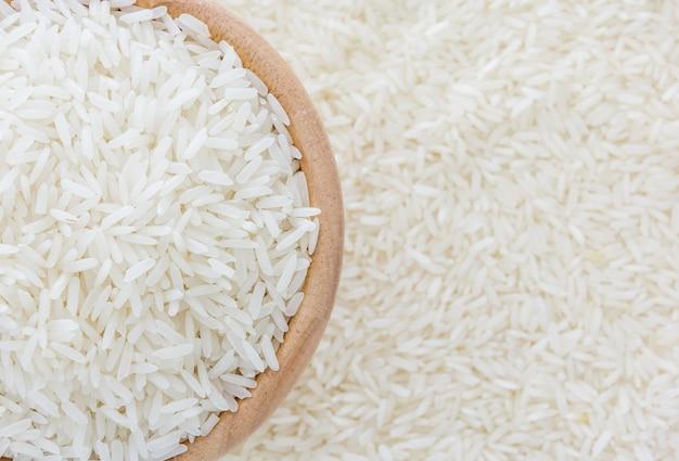 Grãos de arroz de jasmim tailandês em tigela de madeira no fundo de arroz branco