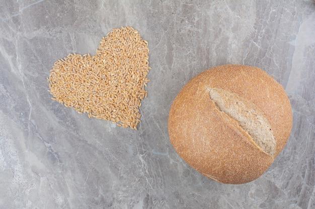 Grãos de aveia crus com pão na superfície de mármore