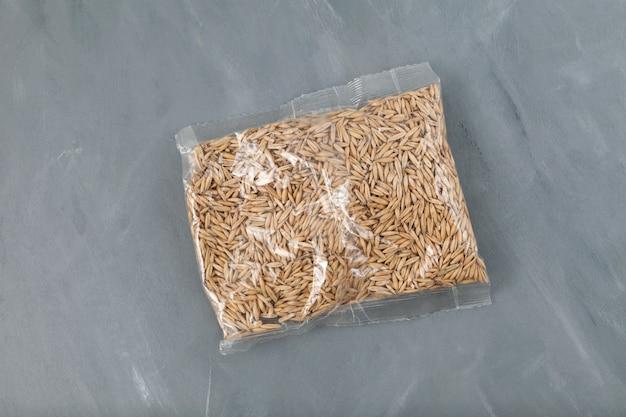Grãos de aveia naturais inteiros em saco plástico transparente.