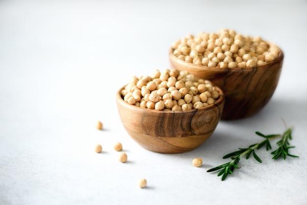 Grãos-de-bico crus orgânicos em umas bacias e em alecrins de madeira no concreto cinzento. ingredientes alimentares saudáveis. copie o espaço.