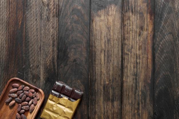 Grãos de cacau e barra de chocolate no fundo de madeira