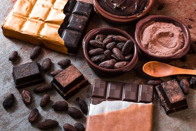 Grãos de cacau e em pó com pedaços de barra de chocolate na mesa