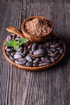 Grãos de cacau secos inteiros na tigela de madeira colher de hortelã
