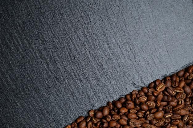 Grãos de café ao lado do fundo do quadro de ardósia