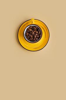 Grãos de café arábica em uma xícara de design amarelo brilhante com pires de papel bege pastel