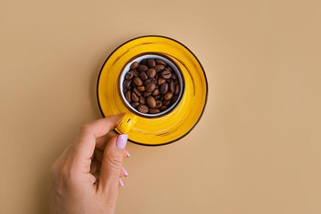 Grãos de café arábica em uma xícara de design amarelo brilhante com pires na mão feminina em um papel bege pastel