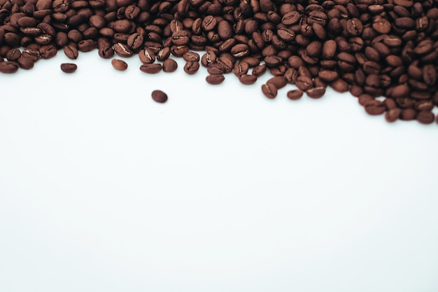 Grãos de café aromáticos marrom-escuros isolados no fundo branco vista superior com espaço de cópia