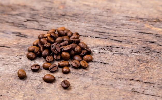 Grãos de café aromáticos na mesa de madeira branca. vista do topo. bandeira