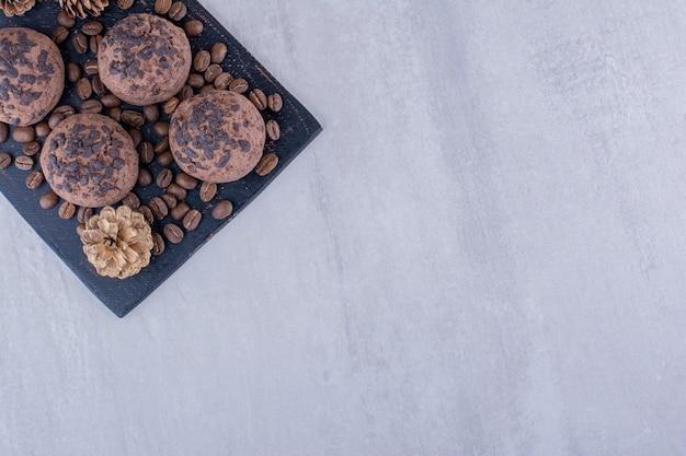Grãos de café, biscoitos e uma pinha em fundo branco.